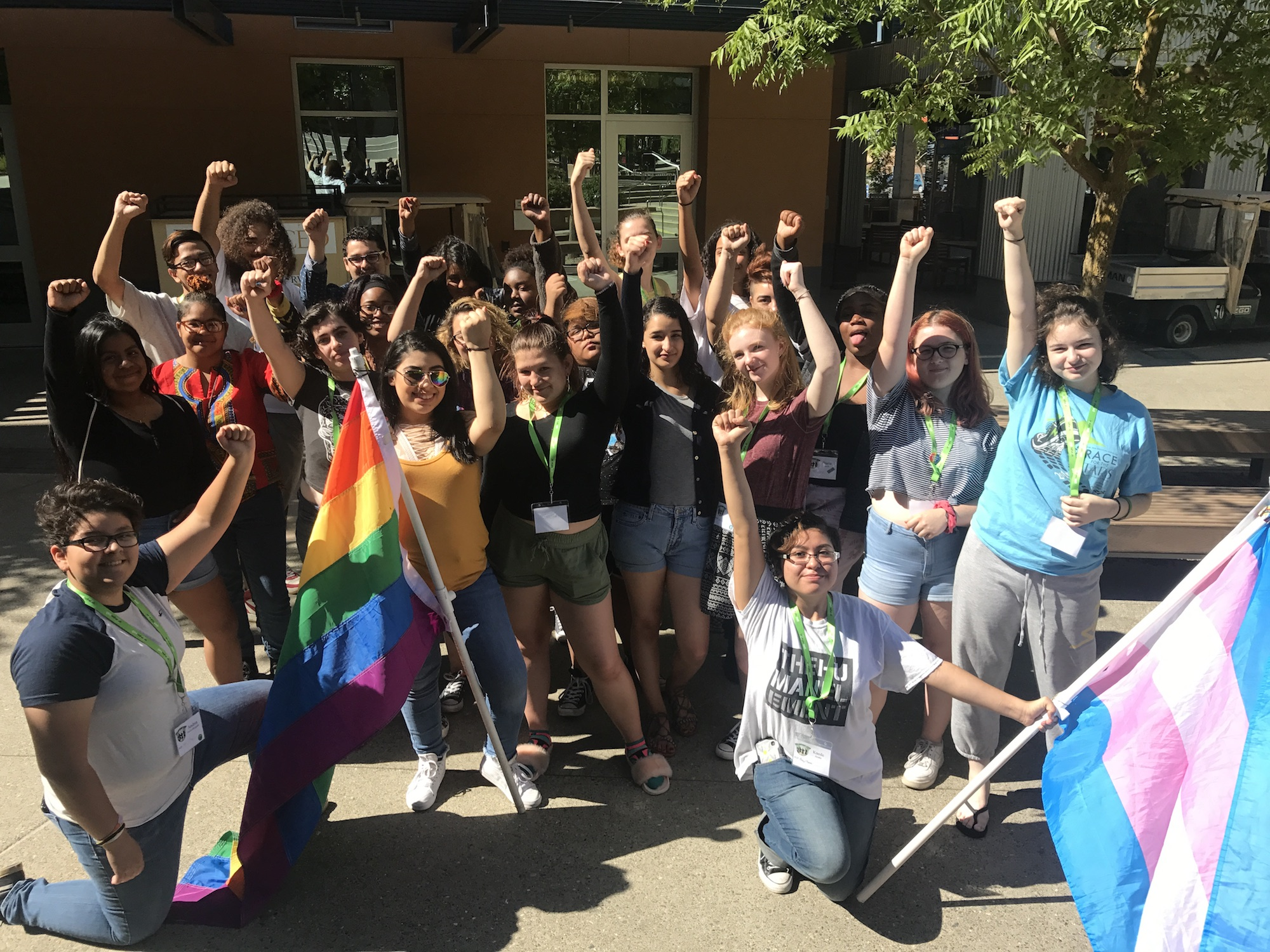 Group of trans and queer young people holding a rainbow pride flag and trans pride flag with fists in the air