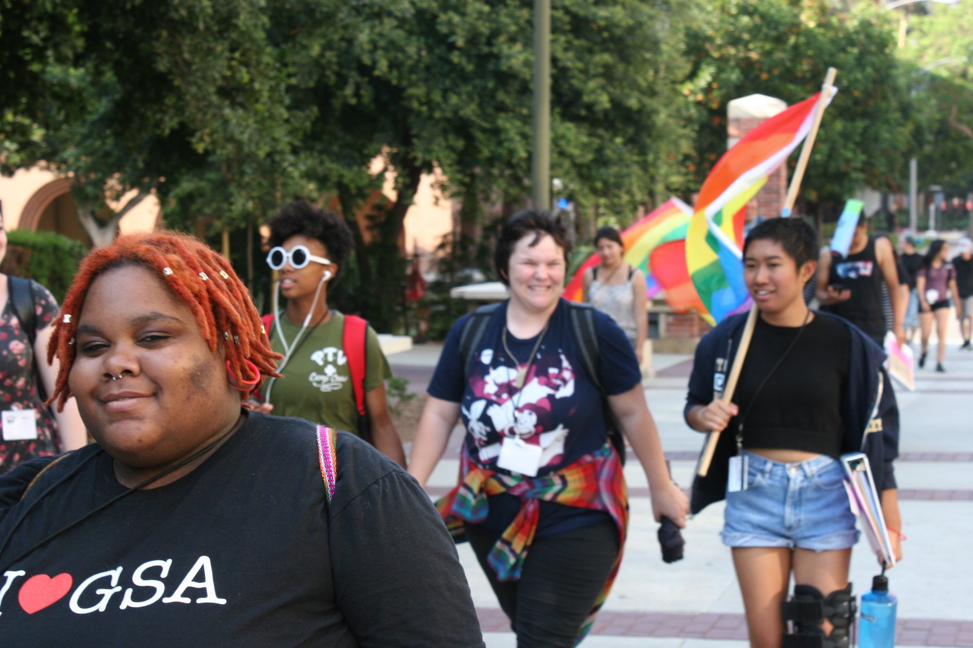 Four trans and queer youth walk along a street. One in the foreground smiles at the camera while wearing a I heart GSA shirt.