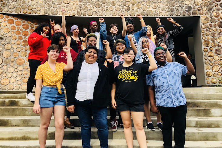 TGNC young people smiling with fists raised in solidarity for racial and gender justice.
